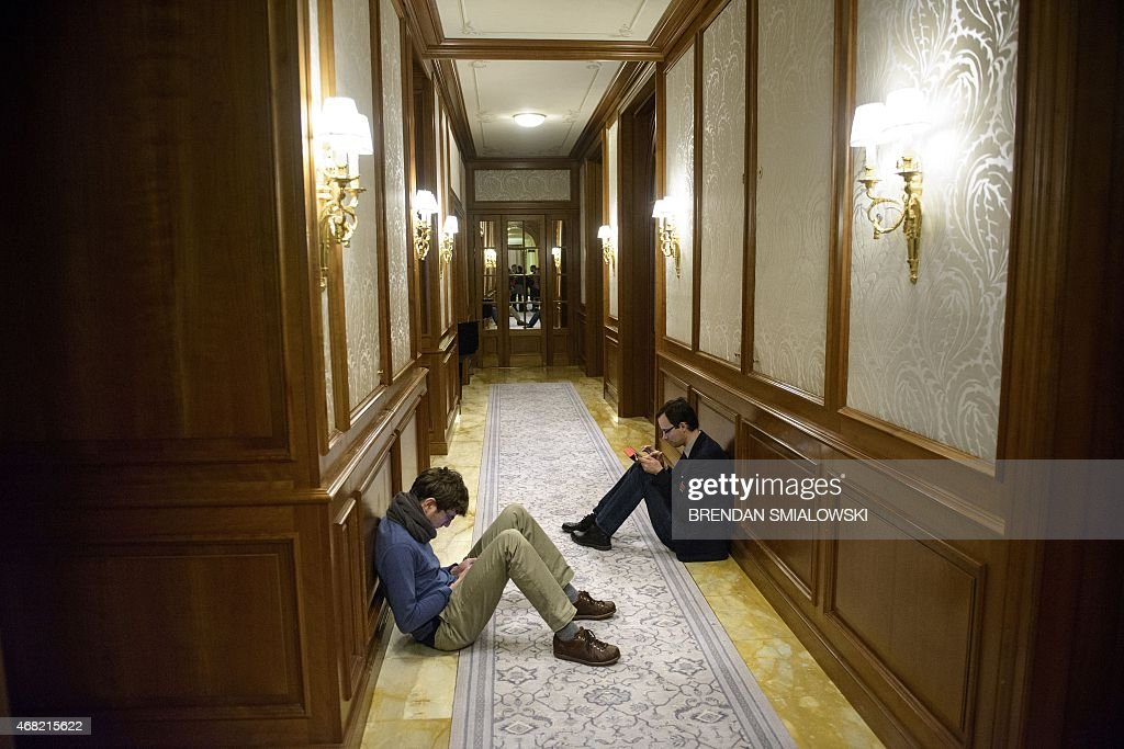 Reporters sit in a hallway as they wait during negotiations on Iran's nuclear programme at the Beau Rivage Palace Hotel in Lausanne Switzerland on...