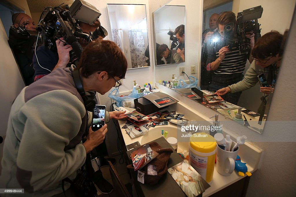 Reporters take pictures of photographs found inside the home of shooting suspect Syed Farook on December 4 2015 in Redlands California The San...