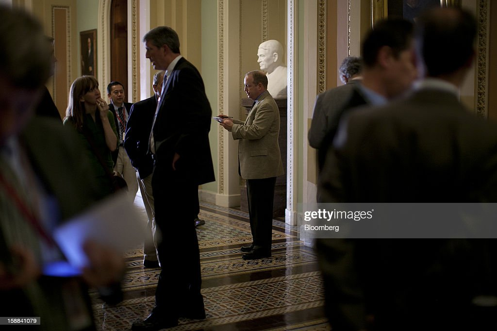Reporters wait for Senators to walk through a corridor of the U.S. Capitol in Washington, D.C., U.S., on Monday, Dec. 31, 2012. Vice President Joe Biden arrived at the Capitol to present a budget deal to wavering Democrats, in advance of a possible vote by 10:30 p.m. tonight, with tax increases for almost every U.S. worker set to start tomorrow. Photographer: Andrew Harrer/Bloomberg via Getty Images