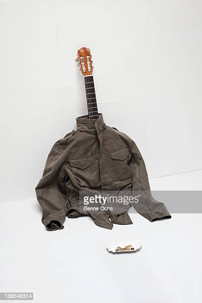 Representation of busker using acoustic guitar inside jacket