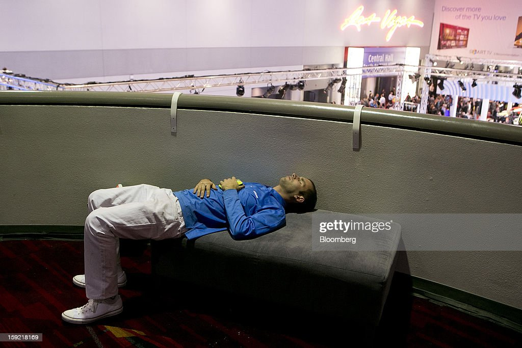 A representative for Samsung Electronics Co. rests during the 2013 Consumer Electronics Show in Las Vegas, Nevada, U.S., on Wednesday, Jan. 9, 2013. The 2013 CES trade show, which runs until Jan. 11, is the world's largest annual innovation event that offers an array of entrepreneur focused exhibits, events and conference sessions for technology entrepreneurs. Photographer: Andrew Harrer/Bloomberg via Getty Images