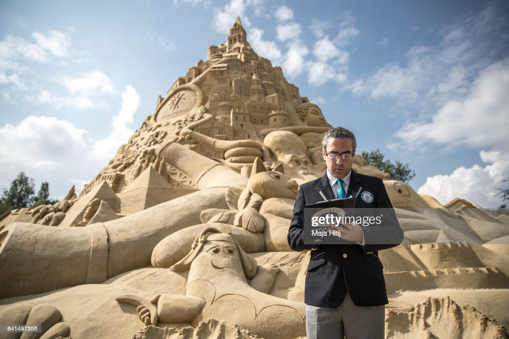 A representative from the Guinness Book of World Records Jack Brockba looks at his notes next to the Sandburg sandcastle on September 1, 2017 in Duisburg, Germany. A local travel agency commissioned the building of the sandcastle and sought to beat the previous world record of 14.84 meters and make it with 16.68 meters to set the new Guinness Book of World Record. The Sandburg took three weeks to build and is made from 3,500 tons of sand.