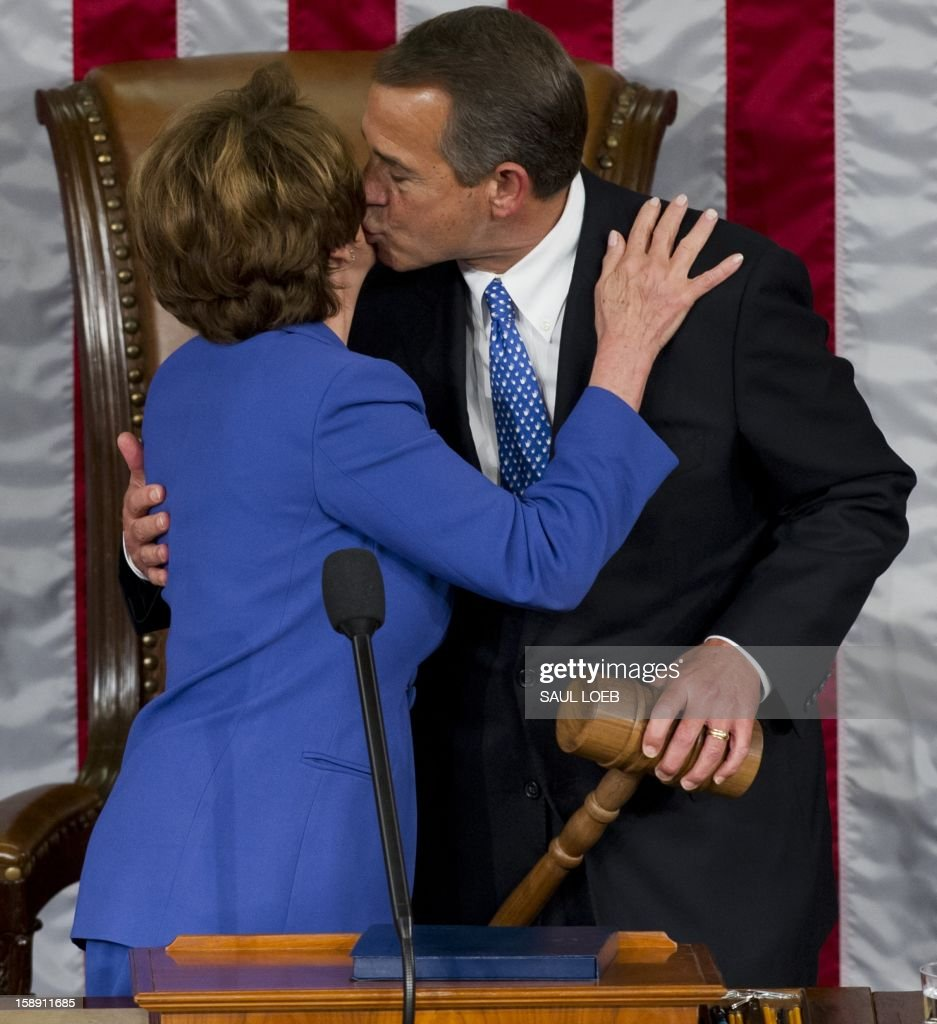 US Representative John Boehner, Republican of Ohio, holds up his gavel after being re-elected as Speaker of the House as he kisses US Representative Nancy Pelosi, Democrat of California and returning Minority Leader, during the opening session of the 113th US House of Representatives at the US Capitol in Washington, DC, on January 3, 2013. AFP PHOTO / Saul LOEB