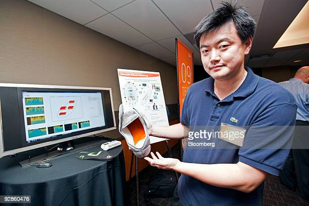 ATT representative Lusheng Ji holds a realtime medical monitoring and diagnosis shoe with wireless capability 'telesole' insoles networked medication...