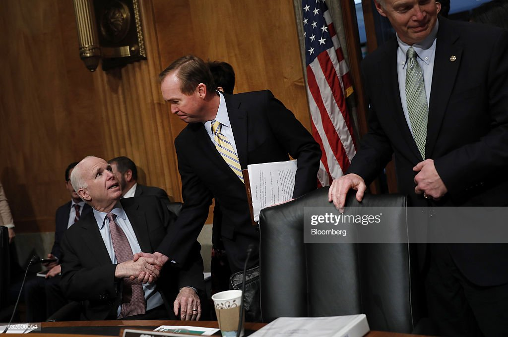Representative Mick Mulvaney, a Republican from South Carolina and Office of Management and Budget director nominee for U.S. President Donald Trump, center, greets Senator John McCain, a Republican from Arizona, before the start of a Senate Governmental Affairs Committee confirmation hearing in Washington, D.C., U.S., on Tuesday, Jan. 24, 2017. Mulvaney said Tuesday the nearly $20 trillion national debt needs to be 'addressed sooner rather than later' and that he would push Trump to break his campaign promises and cut Social Security and Medicare. Photographer: Aaron P. Bernstein/Bloomberg via Getty Images