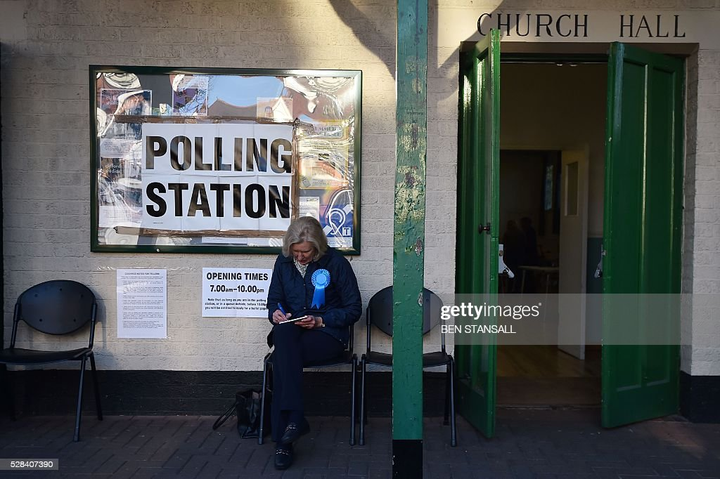 A representative of Britain's Conservative party sits outside a Polling Station in Barnes, south-west London on May 5, 2016. Londoners go to the polls on Thursday to elect their new mayor following a bitter campaign between the two leading candidates, Goldsmith, and Labour's Sadiq Khan, that stayed ugly to the very end. While London chooses a new mayor, there are also elections to the Scottish, Welsh and Northern Irish assemblies, and 124 local authorities scattered across England. / AFP / BEN