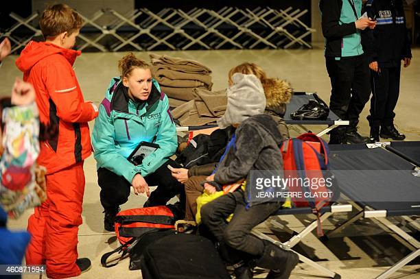 A representative of the Crystal tour operator talks with stranded British holiday makers waiting in a civic hall due to roads being blocked following...