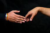 Representative of the LGBT community. Hands reach out for a handshake with a young man. Close-up.