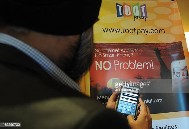 A representative of the Malaysian company Toot shows on May 28 2013 its mobile telephone banking system at the Mobile Money Africa conference in...