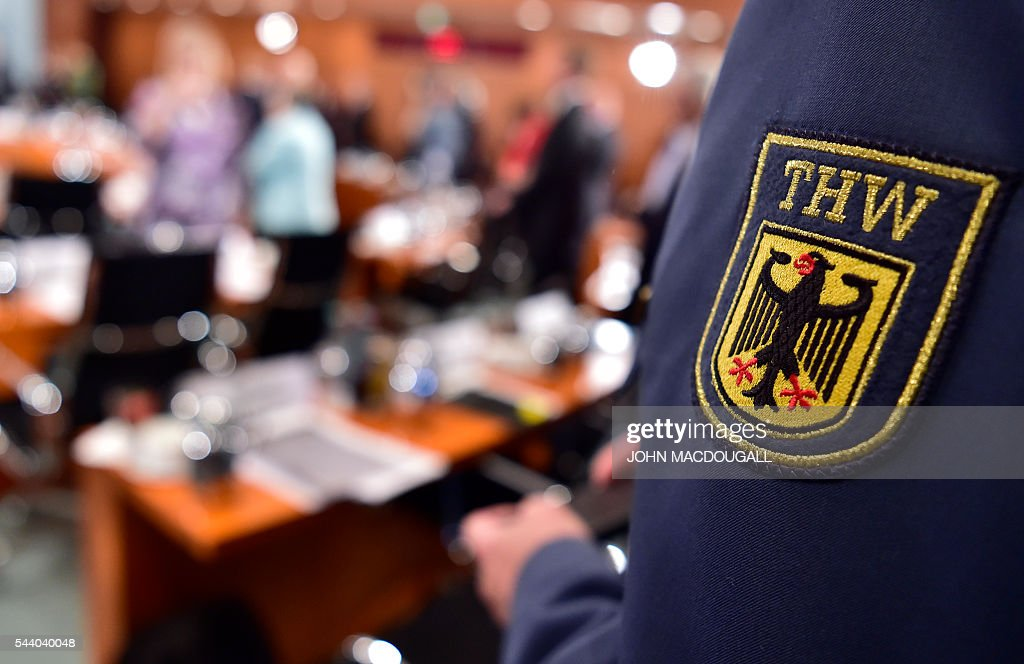 A representative of the Technisches Hilfswerk (THW - Federal Agency for Technical Relief) takes part in a meeting with representatives of associations and organisations involved in helping refugees, at the chancellery in Berlin on July 1, 2016. / AFP / JOHN