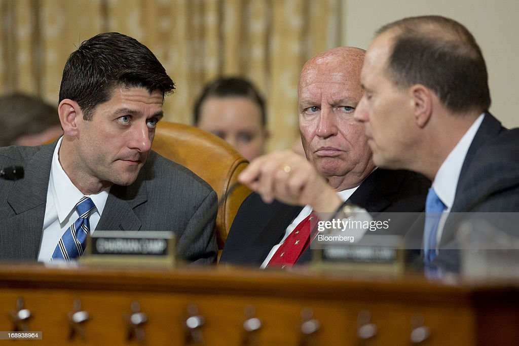 Representative Paul Ryan, a Republican from Wisconsin, left to right, Representative Kevin Brady, a Republican from Texas, and Representative Dave Camp, chairman of the House Ways and Means Committee, talk during a committee hearing in Washington, D.C., U.S., on Friday, May 17, 2013. The scandal at the Internal Revenue Service (IRS) is the 'latest example of a culture of cover-ups' at the agency and in the Obama administration, Camp said. Photographer: Andrew Harrer/Bloomberg via Getty Images