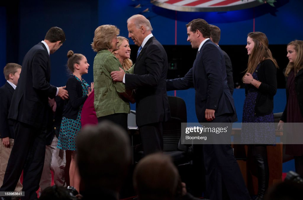 "Representative Paul Ryan, Republican vice presidential candidate, left, and U.S. Vice President Joseph 'Joe' Biden, center, speak with family members after a debate in Danville, Kentucky, U.S., on Thursday, Oct. 11, 2012. Ryan said President Barack Obama is presiding over a ""chaotic"" foreign policy that is 'unraveling'' and making the US. ""less safe,"" as he began his debate tonight with Biden. Photographer: Scott Eells/Bloomberg via Getty Images"