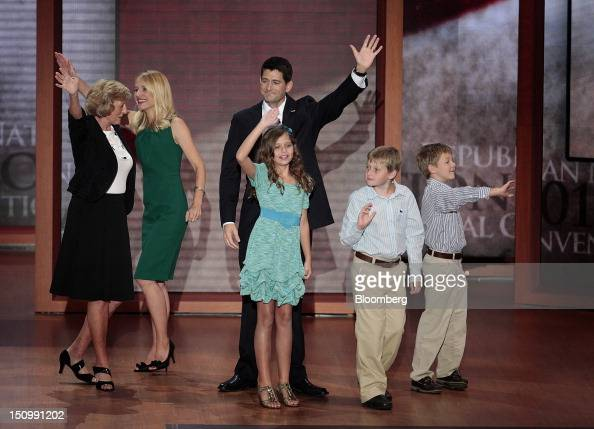 Representative Paul Ryan Republican vice presidential candidate center rear waves on stage after speaking with sons Sam Ryan from right Charlie Ryan...