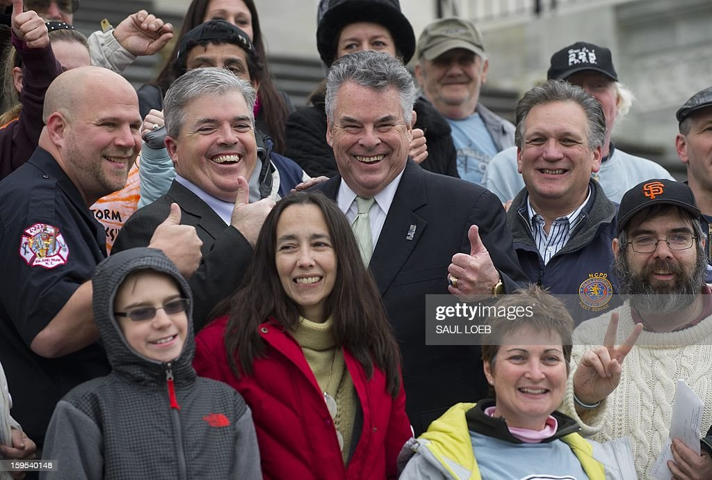 US Representative Peter King (C), Republican of New York, gives a thumbs-up as he stands with New York area first responders and victims of Superstorm Sandy on the steps of the US Capitol in Washington, DC, on January 15, 2013, prior to a vote by the US House of Representatives on a $50.7 billion aid package for victims of the storm. AFP PHOTO / Saul LOEB