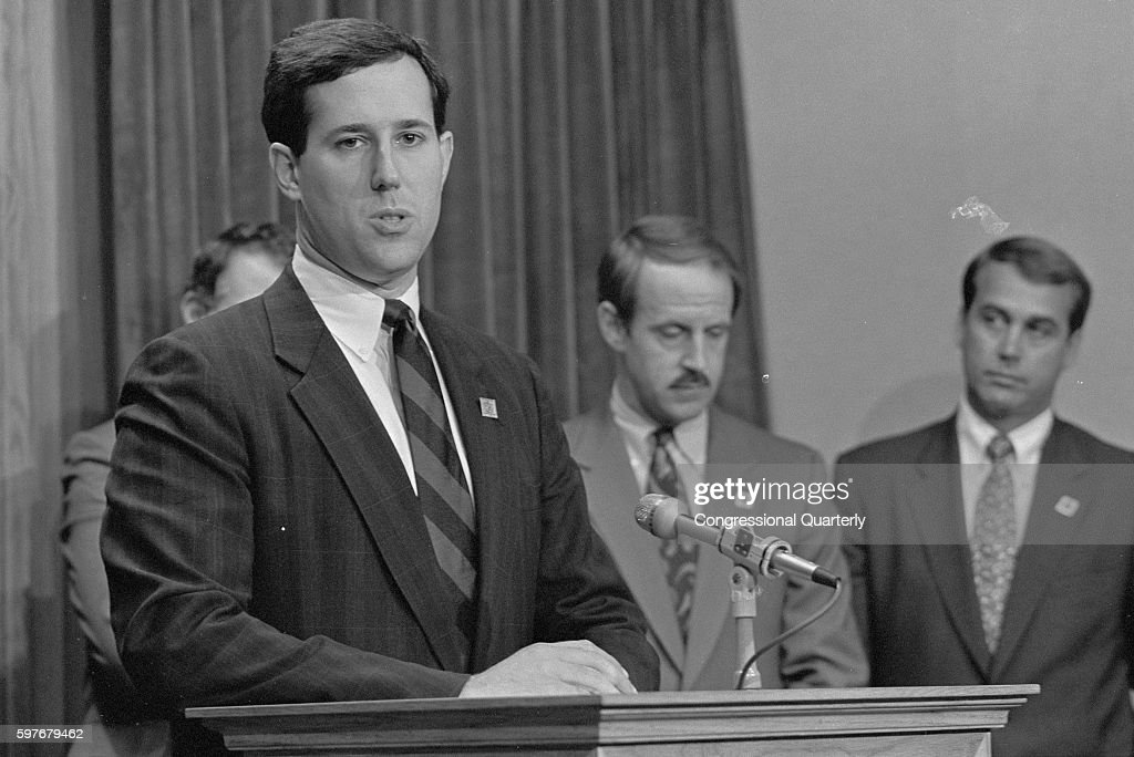 Representative Rick Santorum RPa stands at a podium with Representatives John Boehner and Frank Riggs in September 1991