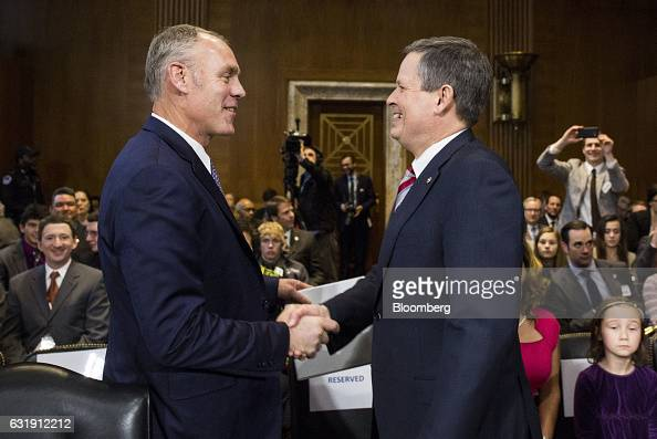 Representative Ryan Zinke US secretary of interior nominee for presidentelect Donald Trump left shakes hands with Senator Steve Daines a Republican...