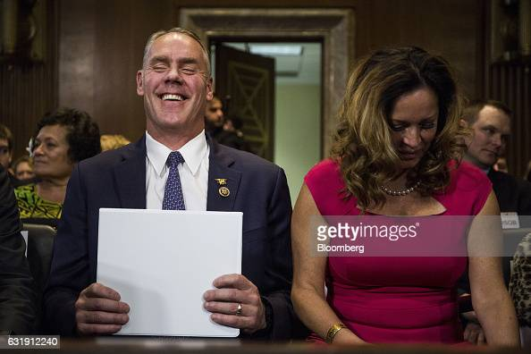 Representative Ryan Zinke US secretary of interior nominee for presidentelect Donald Trump left laughs while sitting next to his wife Lolita Hand...