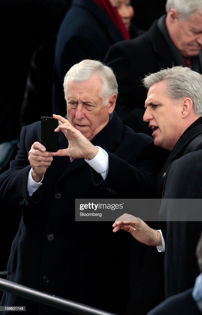 Representative Steny Hoyer, a Democrat from Maryland, left, looks at a photo taken on a smartphone at the Capitol during the U.S. presidential inauguration in Washington, D.C., U.S., on Monday, Jan. 21, 2013. As he enters his second term, President Barack Obama has shed the aura of a hopeful consensus builder determined to break partisan gridlock and adopted a more confrontational stance with Republicans. Photographer: Andrew Harrer/Bloomberg via Getty Images *** Local Caption ** Steny Hoyer