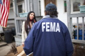 FEMA representative surveys Lori Faillaci left about heat and power availability January 17 2013 in a neighborhood damaged during Hurricane Sandy in...
