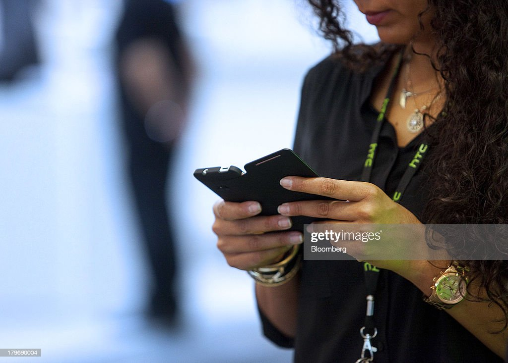 A representative uses a HTC Corp. One mobile phone at the IFA consumer electronics show in Berlin, Germany, on Friday, Sept. 6, 2013. Global smartphone revenue will rise 22 percent in 2013, or nearly half the pace of an expected 41 percent gain in shipments, amid falling prices, according to UBS. Photographer: Krisztian Bocsi/Bloomberg via Getty Images