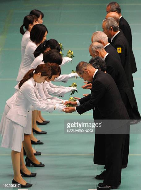Representatives of bereaved families receive flowers before offering flowers to the altar during an annual memorial service to honour the dead on the...