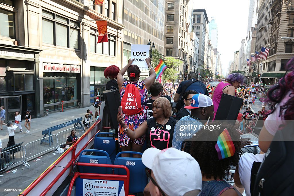 Representatives of Housing Works ride aboard a double decker bus during the 2016 LGBT Pride March on June 26, 2016 in New York City.