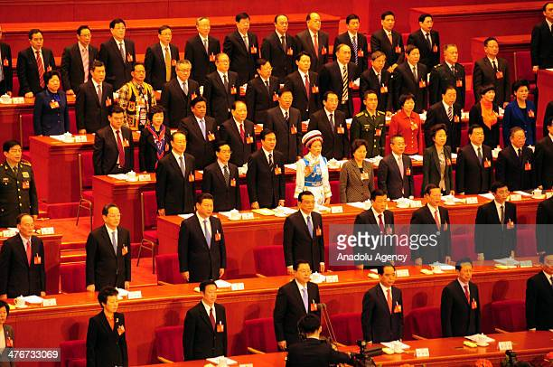 Representatives stand in silence for those who lost their lives as a result of the mass stabbing at a Chinese railway station in Kunming city on...