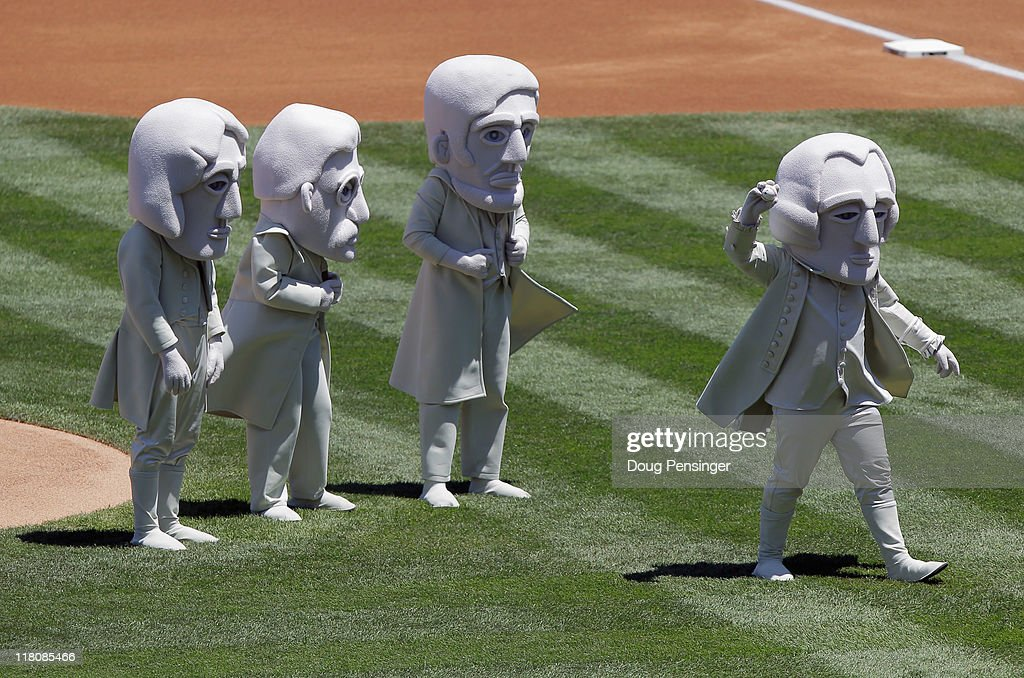 Representing the US Presidents sculpted on Mount Rushmore, George Washington (R) throws out the ceremonial first pitch as (L-R) Thomas Jefferson, Theodore Roosevelt and Abraham Lincoln look on as the Kansas City Royals prepare to face the Colorado Rockies during Interleague play at Coors Field on July 3, 2011 in Denver, Colorado.
