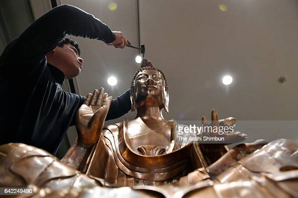 A reproduction team member puts the finishing touches to the Gautama Buddha statue replica at the Tokyo University of the Arts Ueno campus on...