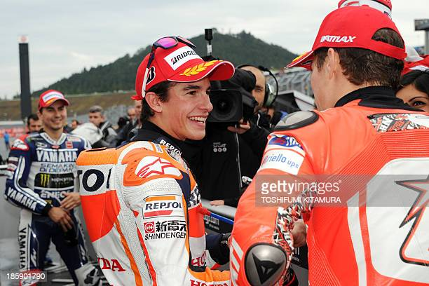 Repsol Honda team rider Marc Marquez of Spain chats with Ducati team rider Nicky Hayden of the US at the parc ferme while Yamaha Factory Racing rider...