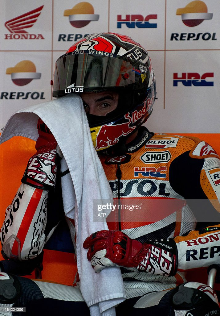 Repsol Honda Team rider Marc Marquez of Spain wipes his sweats during the fourth practice session at the Malaysian Grand Prix MotoGP motorcycling race at Sepang on October 12, 2013.