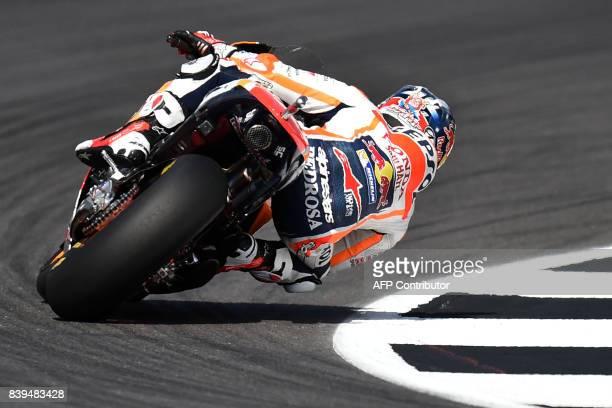 Repsol Honda Team's Spanish rider Dani Pedrosa rides through Woodcote Corner during the fourth free practice session of the British Grand Prix...