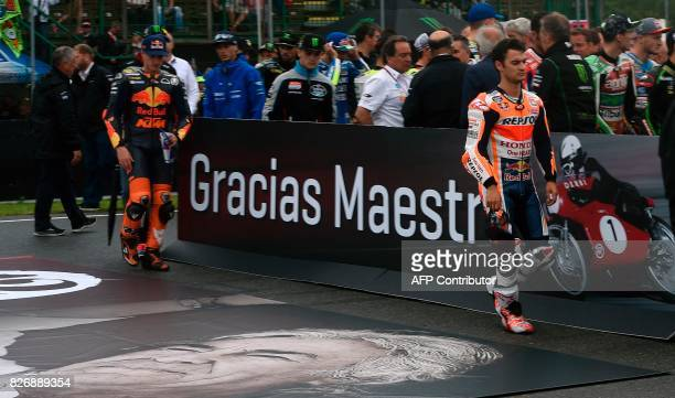 Repsol Honda Team's Spanish rider Dani Pedrosa walks past the banner after members and riders of Moto3 Moto2 and MotoGP held a minute of silence for...