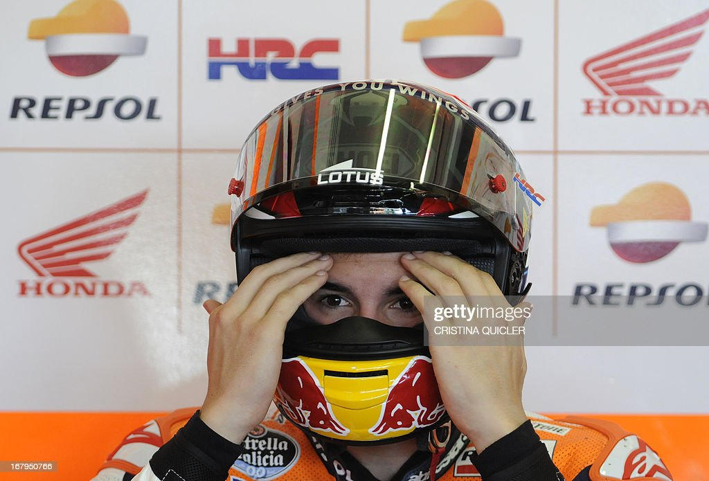 Repsol Honda Team's Spanish rider Marc Marquez adjusts his helmet before taking part in the second MotoGP free practice of the Spanish Grand Prix at the Jerez racetrack in Jerez de la Frontera on May 3, 2013. AFP PHOTO / CRISTINA QUICLER
