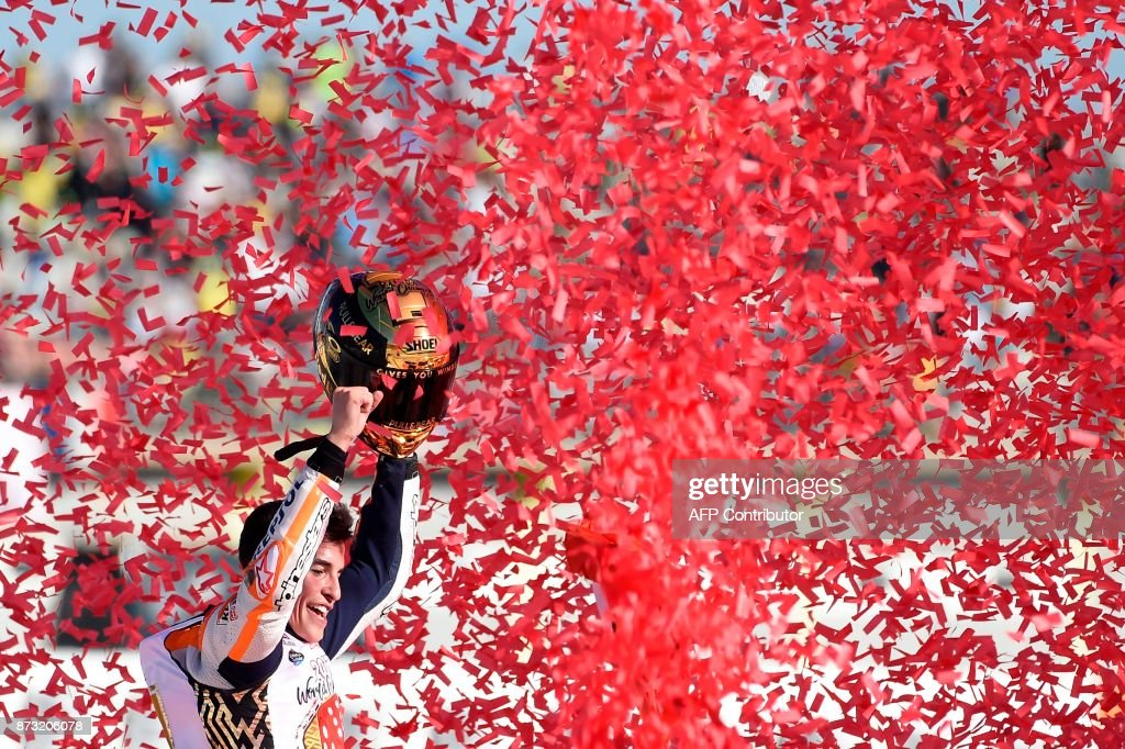 TOPSHOT - Repsol Honda Team's Spanish rider Marc Marquez celebrates after the MotoGP race of the Valencia Grand Prix at Ricardo Tormo racetrack in Cheste, near Valencia on November 12, 2017. Spain's Marc Marquez sealed his sixth world championship and fourth in the premier MotoGP category with third place at the Valencia Grand Prix. Marquez's Honda teammate Dani Pedrosa won the race from France's Johann Zarco in second. JORDAN