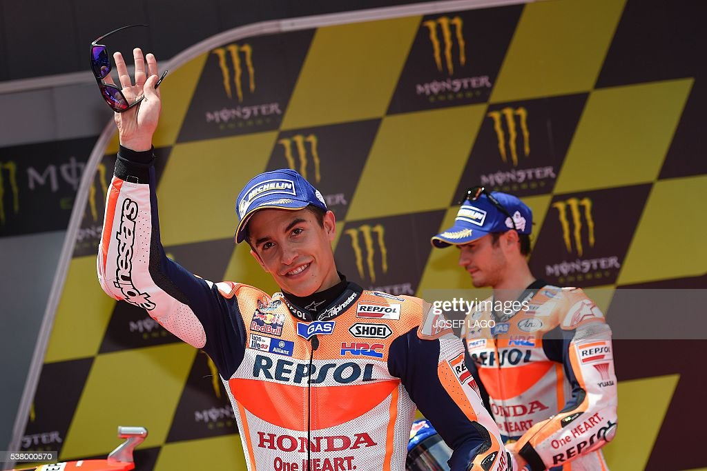 Repsol Honda Team's Spanish rider Marc Marquez (L) celebrates his pole position during the MotoGP qualifying session at the Catalunya racetrack in Montmelo, near Barcelona, on June 4, 2016. / AFP / JOSEP