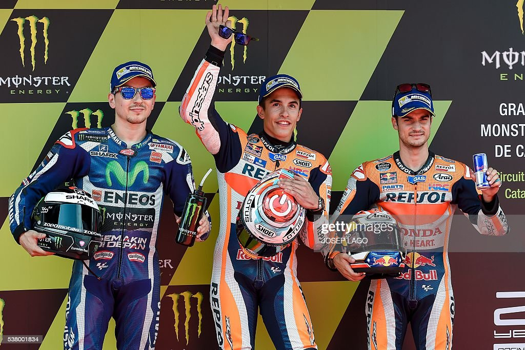 Repsol Honda Team's Spanish rider Marc Marquez (C) celebrates his pole position with Movistar Yamaha MotoGP's Spanish rider Jorge Lorenzo (L), second and Repsol Honda Team's Spanish rider Daniel Pedrosa, third during the MotoGP qualifying session at the Catalunya racetrack in Montmelo, near Barcelona, on June 4, 2016. / AFP / JOSEP