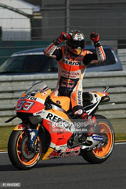 Repsol Honda Team's Spanish rider Marc Marquez celebrates his win at the MotoGP Japanese Grand Prix and for securing his third world championship...
