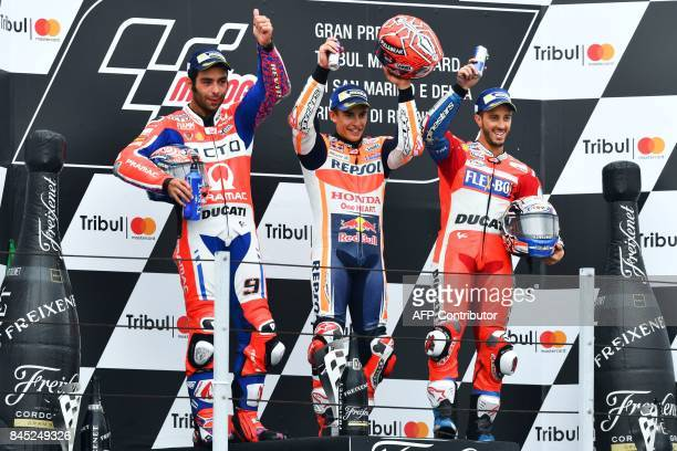 Repsol Honda Team's Spanish rider Marc Marquez celebrates winning on the podium to secondplaced Ducati Team's Italian rider Danilo Petrucci and...