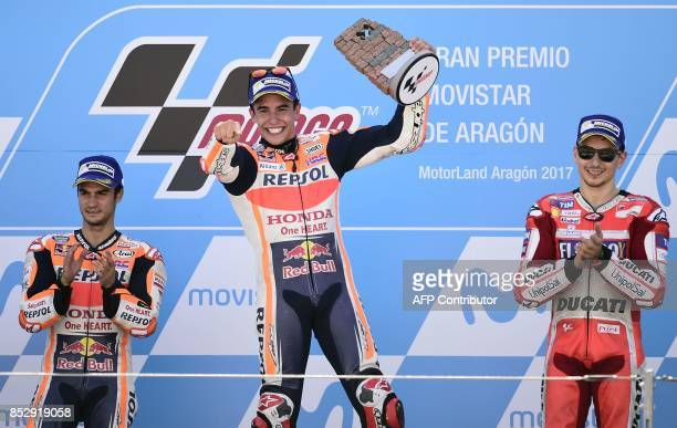 Repsol Honda Team's Spanish rider Marc Marquez celebrates winning on the podium between second placed Repsol Honda Team's Spanish rider Dani Pedrosa...