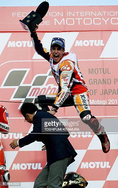 Repsol Honda Team's Spanish rider Marc Marquez gestures on the podium as he celebrates his fifth world champion after his victory at the MotoGP race...