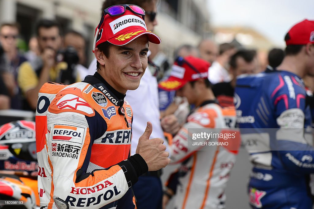 Repsol Honda Team's Spanish rider Marc Marquez gives the thumbs up after taking pole position following the MotoGP qualifying session of the Aragon Grand Prix at the Motorland racetrack in Alcaniz on September 28, 2013.