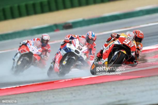 Repsol Honda Team's Spanish rider Marc Marquez leads ahead of Ducati Team's Italian rider Danilo Petrucci and Ducati Team's rider Italian Andrea...
