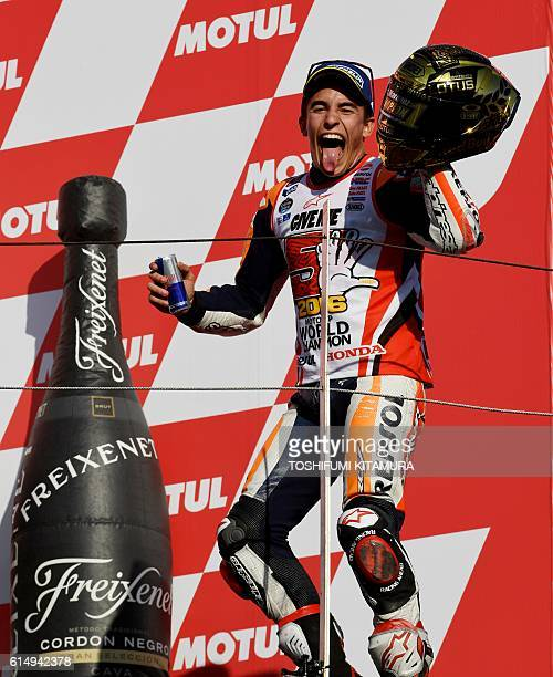 Repsol Honda Team's Spanish rider Marc Marquez reacts as he enters the podium after his victory at the MotoGP race at the Japanese Grand Prix in the...