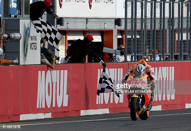 Repsol Honda Team's Spanish rider Marc Marquez receives the checkered flag to win the MotoGP race at the Japanese Grand Prix in the Twin Ring Motegi...