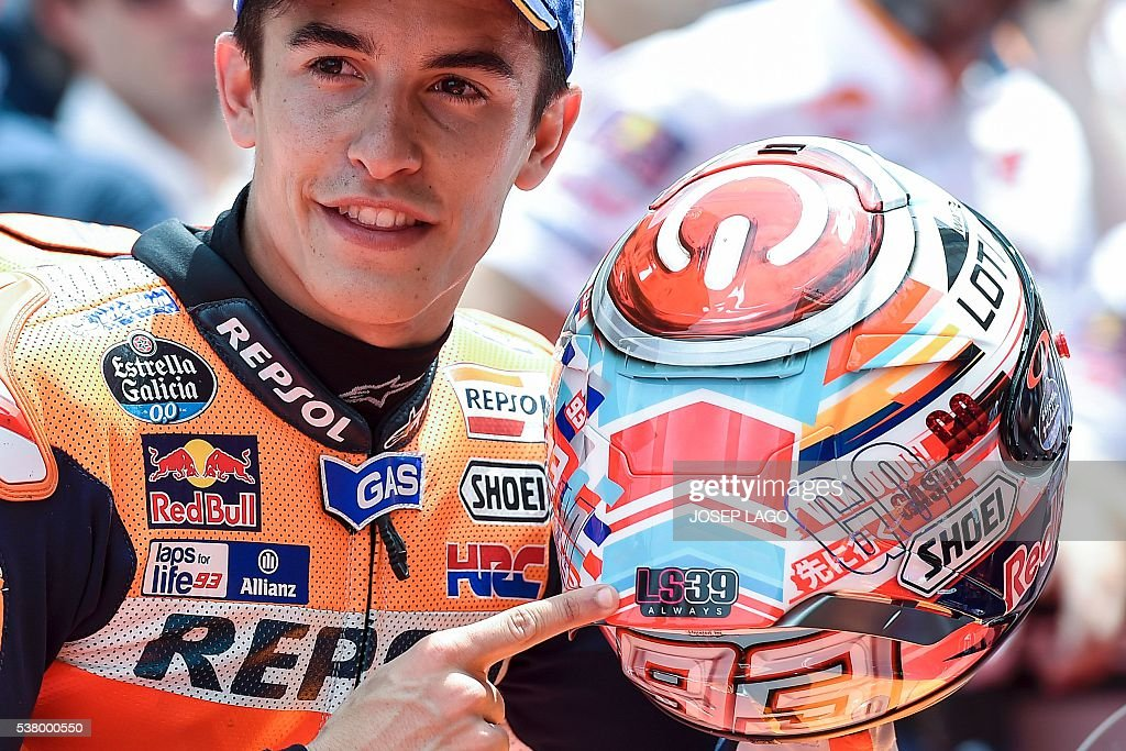 Repsol Honda Team's Spanish rider Marc Marquez shows a sticker on his helmet as a tribute for SAG Team Moto2's Spanish rider Luis Salom while celebrating his pole position during the MotoGP qualifying session at the Catalunya racetrack in Montmelo, near Barcelona, on June 4, 2016. / AFP / JOSEP