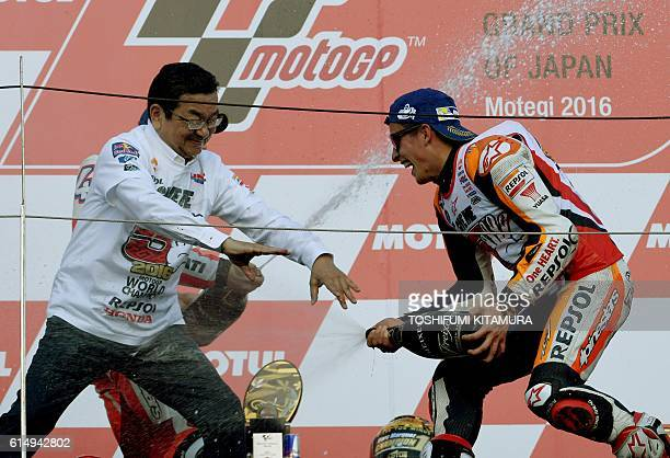 Repsol Honda Team's Spanish rider Marc Marquez sprays champagne at Honda Motors president and CEO Takahiro Hachigo on the podium after his victory at...