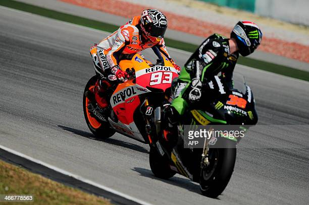 Repsol Honda Team's Spanish rider Marc Marquez steers his bike as Monster Yamaha Tech 3's British Bradley Smith looks back during the first MotoGP...