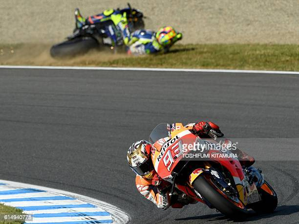 TOPSHOT Repsol Honda Team's Spanish rider Marc Marquez takes a corner as Movistar Yamaha MotoGP's Italian rider Valentino Rossi crashes out of the...