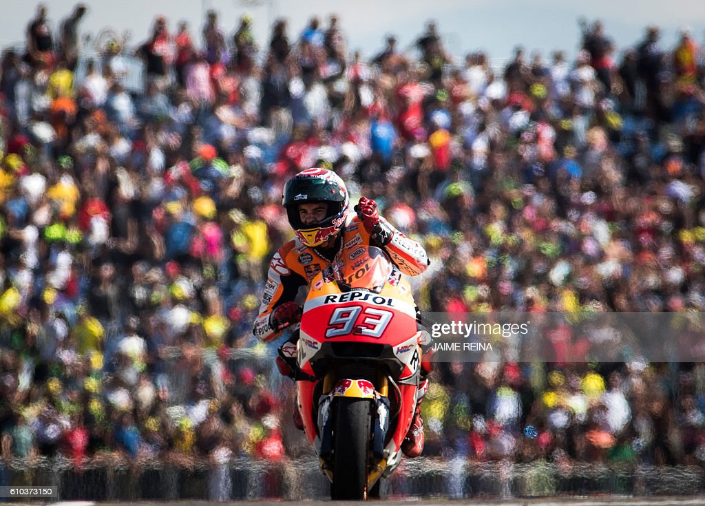TOPSHOT - Repsol Honda's Spanish rider Marc Marquez celebrates after winning the Moto GP race of the Aragon Grand Prix at the Motorland racetrack in Alcaniz on September 25, 2016. / AFP / JAIME